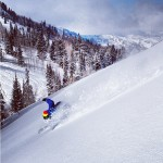 A snowboarder boarding down hill at Powder Mountain with Powder Mountain Shuttle